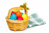 Baked basket with Easter colored eggs and bunch of pussy-willow