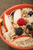 Bowl of delicious steel cut oats with fresh fruit, nuts honey