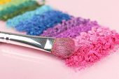 Rainbow crushed eyeshadow and professional make-up brush on pink background