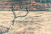 picture of olive shaped  - A simple beaded olive wood cross or rosary rests upon a rustic table laid out in the shape of a heart - JPG