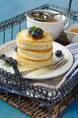 A Stack Of Scotch Pancakes With With Honey And Blueberries On Tray