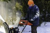 Senior Man Behind A Snowblower