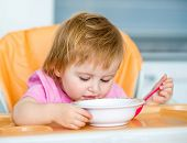one year old girl in a highchair for feeding with a spoon and a plate in the kitchen at home