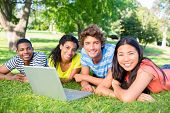 Portrait of university students with laptop lying on grass on college campus