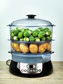 Healthy food in steamer, steam cooker with brussels sprouts and potato
