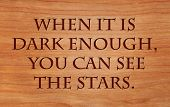 When it is dark enough, you can see the stars. - quote by Ralph Waldo Emerson on wooden red oak background