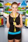 Healthy cheerful girl holding in hand bowl with fresh tasty green salad, dietitian recommending eati
