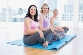 Happy pregnant women sitting in yoga class in a fitness studio