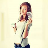 Beautiful young woman holding euros bills and house model