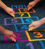 stock photo of child development  - Community development education and children learning concept with a group of hands representing ethnic groups of young people holding chalk cooperating together as friends to draw a playground hopscotch game - JPG