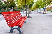stock photo of neat  - Red bench on neat and clean pedestrian sidewalk in Italy - JPG