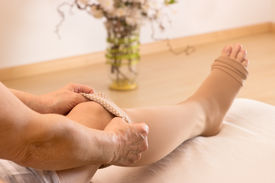 stock photo of stocking-foot  - A female puts some antithrombotic stockings on - JPG