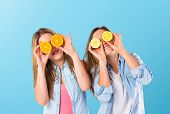 Friends Playing With Fruits Over Blue Background