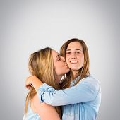 Girl Giving Kiss At Her Sister Over Grey Background