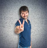 Man Doing Victory Gesture Over Textured Background