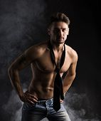 Handsome Shirtless Muscular Man Standing On Dark Background