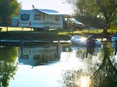 stock photo of trailer park  - Camping site on a lake with caravans and boats - JPG