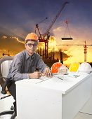 Engineering Man With Safety Helmet Working Table Against Building Construction Background