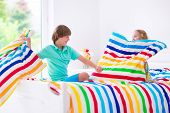 pic of pillow-fight  - Two children happy laughing boy and cute curly little girl having fun at pillow fight with feathers in the air jumping laughing and giggling in a white bedroom with colorful bedding - JPG