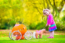 stock photo of cinderella  - Cute curly little girl playing Cinderella fairy tale holding a magic wand next to a pumpkin carriage having fun in an autumn park at Halloween - JPG