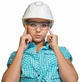 Woman in hard hat and protective glasses