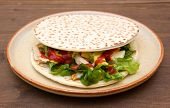 Flatbread with chicken and salad on wood