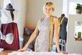 Pretty dressmaker at work pinning dress on dummy