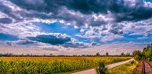 Spring landscape with field, rail road and clouds Spring background