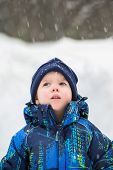 Boy Looking Up In Wonder At Snow Falling