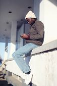 Street Fashion And Technology Concept - Lifestyle Stylish Young African Man Using Smartphone In The