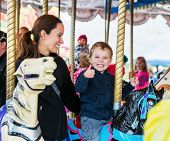 image of carnival ride  - A happy mother and son are riding on a carousel together smiling and having fun at an amusement park - JPG