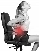 Businesswoman with lower back pain, sitting on office chair