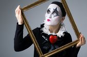 stock photo of harlequin  - Woman in disguise harlequin in the picture frame - JPG