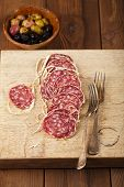 Dried french sausages salami on wooden platter, rustic style