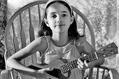 image of musical instrument string  - HIspanic child playing her favorite musical instrument - JPG