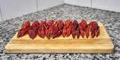 picture of craw  - Nine red river crayfish on cutting board on grey granite worktop in front perspective - JPG