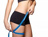 foto of upper thigh  - Young woman with measuring tape measures the upper thigh - JPG