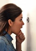 Surprised young woman looking out through the peephole of her front door.