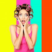Beautiful girl in hair curlers on colorful background