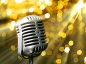 Silver retro microphone on golden festive background