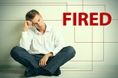 Sad fired office worker sitting on floor on wall background