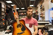 music, sale, people, musical instruments and entertainment concept - male assistant or customer with beard holding acoustic guitar at music store