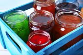Homemade jars of fruits jam in crate on color wooden table background