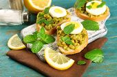 Sandwiches with green peas paste and boiled egg on cutting board with napkin on color wooden background