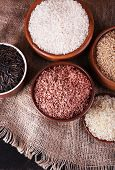 Different kinds of rice in bowls on sackcloth background