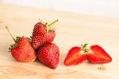 The fresh strawberry on fruit wood table.