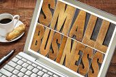small business text in letterpress wood type printing blocks on a laptop with a cup of coffee