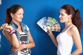 Two Young beautiful weman holding color palette with color samples.