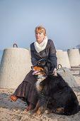 Dog And Woman Sitting Near Sea