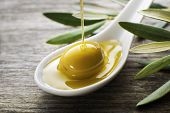 stock photo of spooning  - Olive oil pouring on the spoon close up - JPG